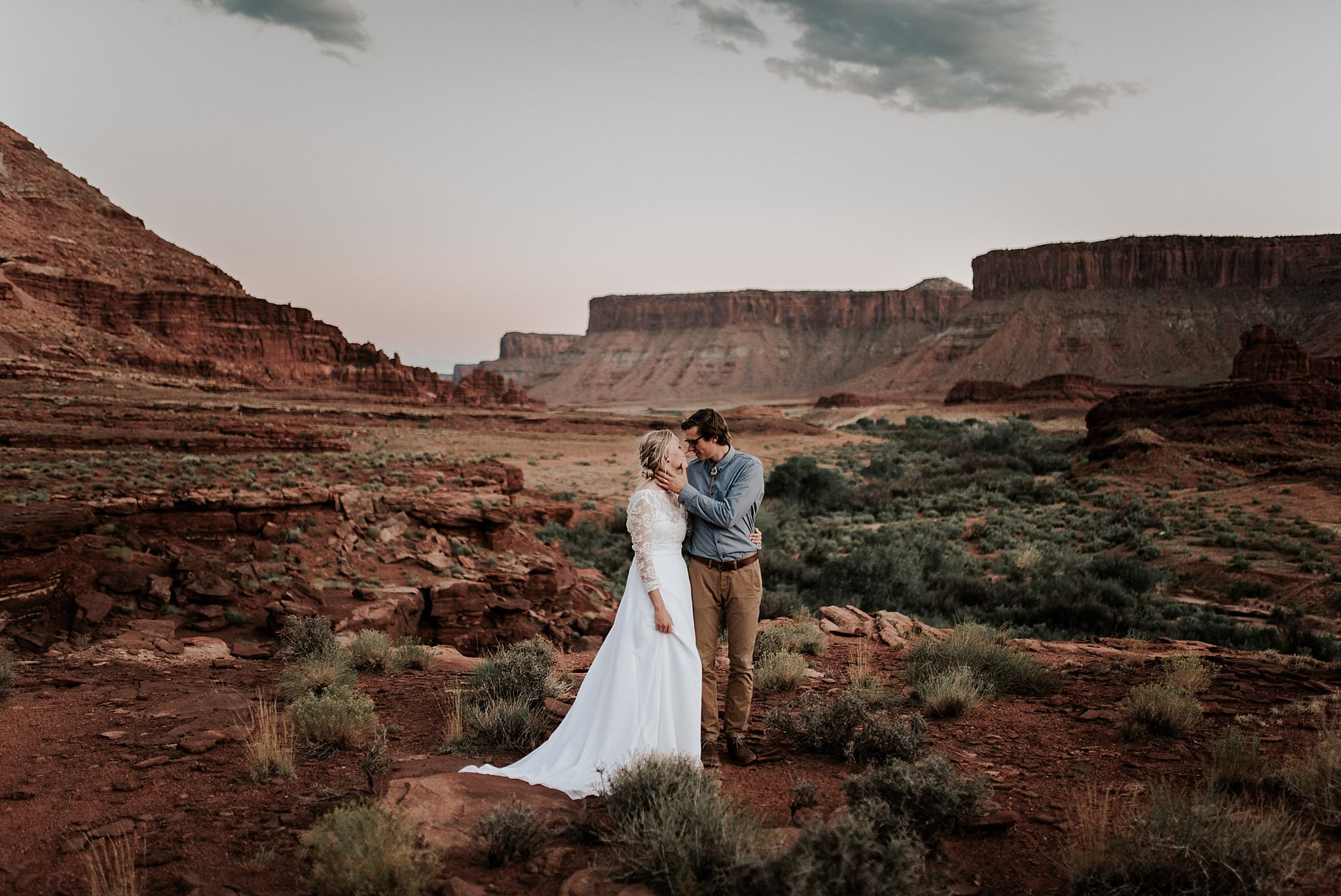 Wedding couple hiking through the Utah desert after getting married