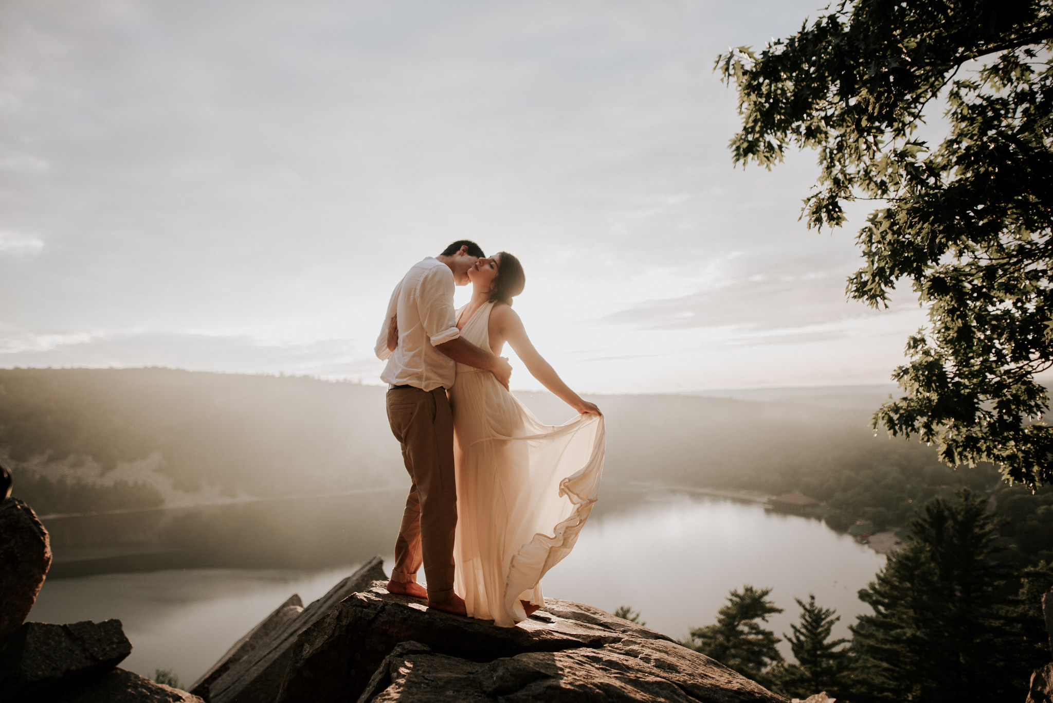 bride-and-groom-standing-on-cliff-overlooking-sunset-with-dress-flipping-while-embracing